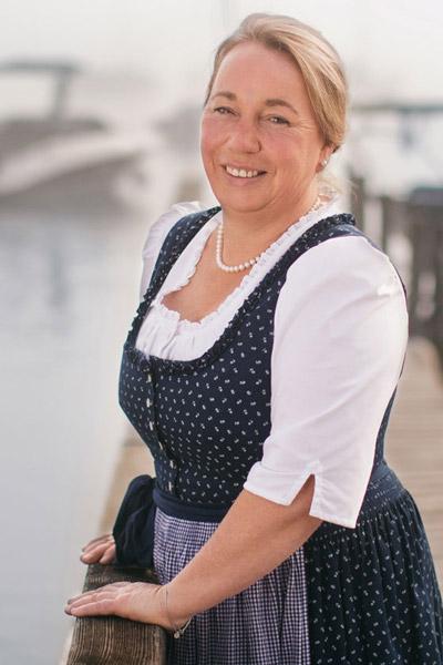 Frau Marlene Greinwald im dunkelblauen Dirndl am Bootssteg
